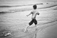 Boy running the morning surf