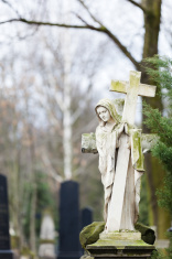 Statue of Virgin Mary with cross on cemetary.
