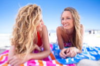 Two teenage girls gossip and sunbathe on Muizenberg beach