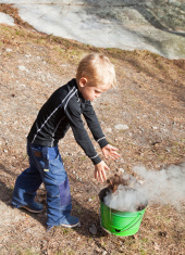 Little blond boy burning old leaves.
