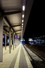 Abandoned railroad station platform at night