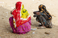 Two indian women squatting