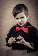 deviant young sailor boy with cigar wood background and table