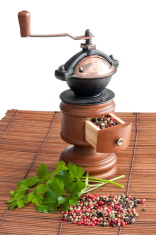 Pepper grinder, different sort of peppers and some parsley leave