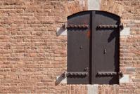 iron window shutters in a brick wall