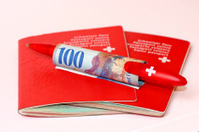 Two Swiss passports with money and pencil