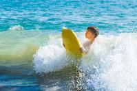 teen boy has fun surfing in the waves