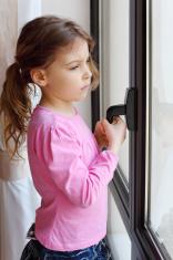 Little sad girl stands near window