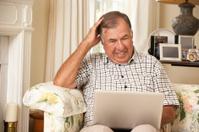 Frustrated Retired Senior Man Sitting On Sofa Using Laptop