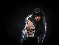Color Rocker Leaning Forward posing with Human Skull Black Backg