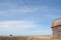 Jet trails in vast wide open prairie blue sky