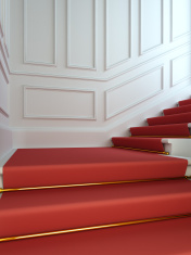 Classical staircase with a red carpet.