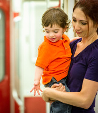 Mother Holding Son on Subway Train