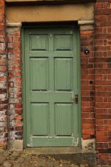 Old green panelled door and brickwork.