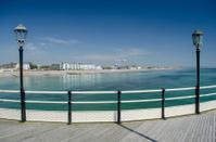 pier deck view of ocean between lamp poles