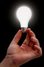 Hand Holding Lit Light Bulb