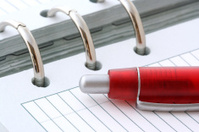 Red Ballpoint Pen on Notebook