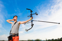 Young archer training target shooting