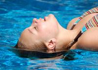 Teen girl laying head back in pool