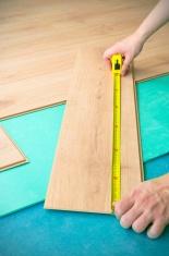 Repair of a floor covering. Man measure panel