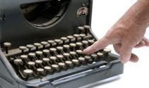 Finger pushing a key on vintage typewriter