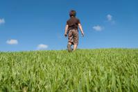 kid walking away in grass