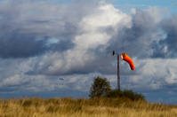 Windsock on skyline with distant aircraft