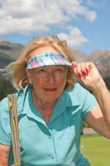 Female Senior Citizen Lining Up Golf Putt
