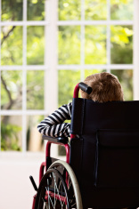 Backview of boy in wheelchair looking longingly through window