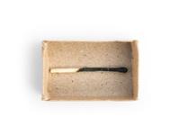matchbox with a burnt matchstick