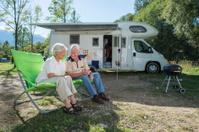 Senior couple having fun camping with camper van