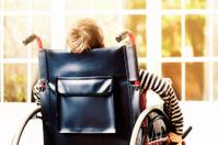 Little boy wheels his wheelchair towards sunny window