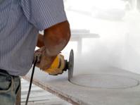 man cutting granite