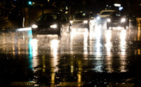 Rainy street with night traffic in Milan, Italy