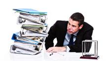 Unhappy businessman grimaces at enormous pile of files