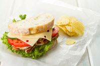 Prosciutto Sandwich With Chips On Waxed Paper