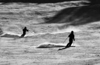 backlit sihouette skiers