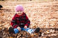 Little girl sitting among leaves