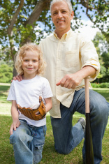 Father and son smiling holding baseball bat