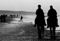 Silhouettes of horseriders on the beach.