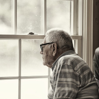 Wistful Senior Man Looking Through Grungy Window