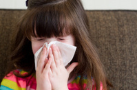 LIttle girl blows her nose with a tissue