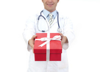 Smiling medical doctor holding gifts in hands