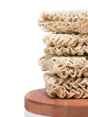 Ramen instant raw noodles staked on wooden plank side border