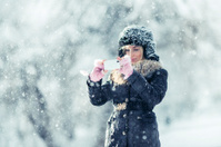 Young woman outdoor photographing snow on a winter day
