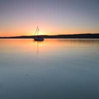 Sailboat on Calm Lake at Sunrise