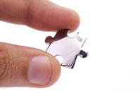 Hand holding a jigsaw piece