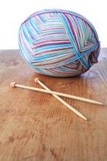 merino wool skein and knitting needles