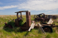 Rusty old pickup truck and some junk in a field