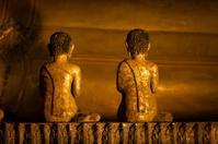 Statues of Monks Praying Next to Buddha